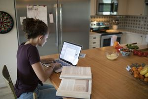 A student sitting at a kitchen table with a laptop and a number of textbooks