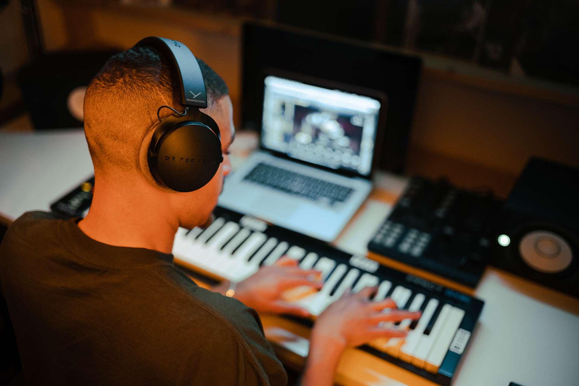 Man using Beyerdynamic DT 700 Pro X with keyboard and studio