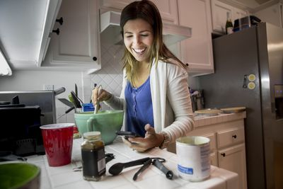 A woman using her iPhone as she makes a recipe in the kitchen.