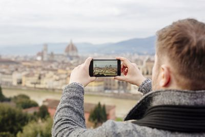 Tourist photographing Florence skyline with his smart phone
