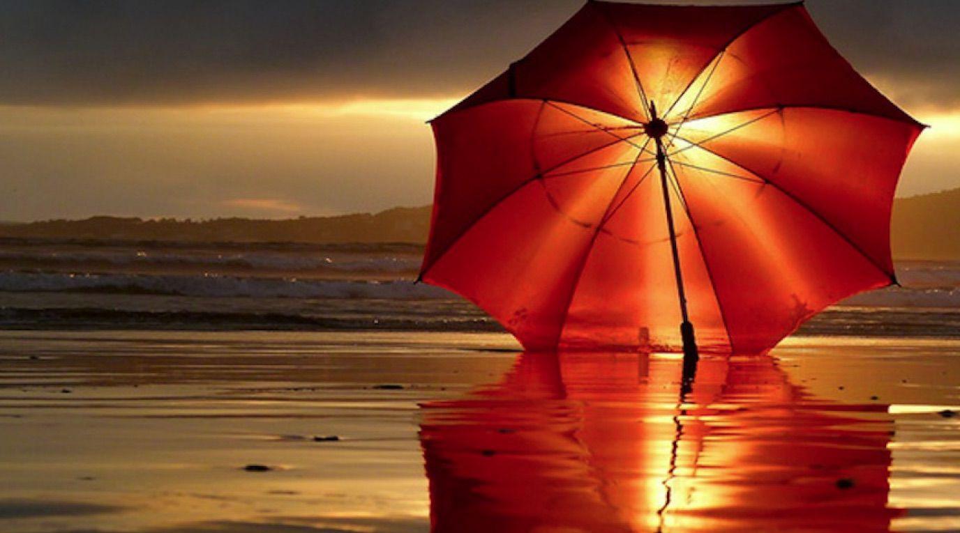 Free beach wallpaper featuring a red beach umbrella at sunset