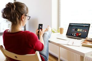 A woman using Plex on her phone, with a laptop running Plex Media Server.