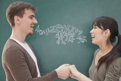 Man and woman saying how are you in different languages while holding hands