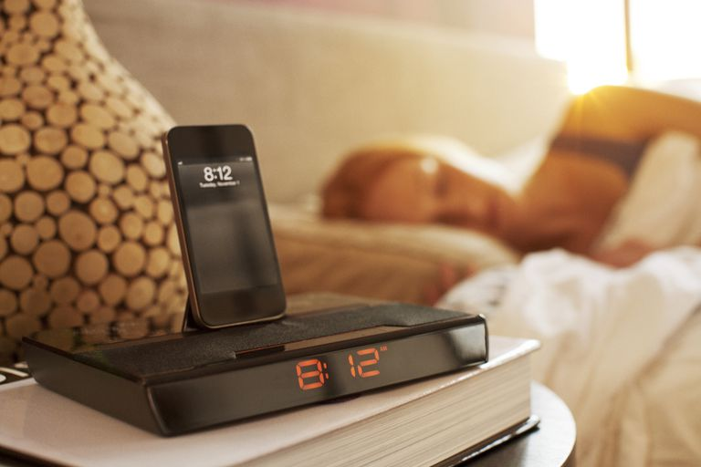 Woman sleeping next to phone alarm clock