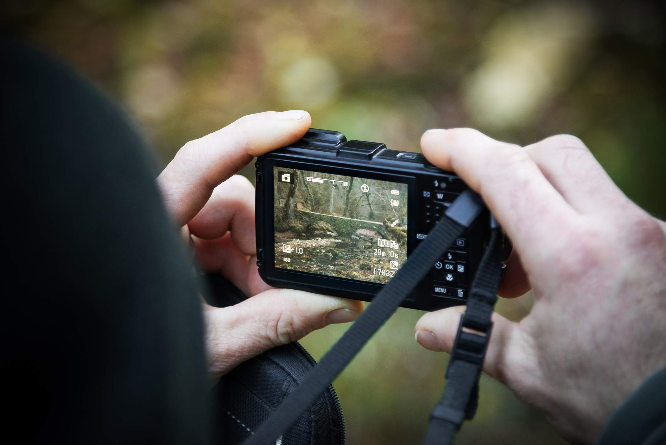 A man using a small point and shoot camera.