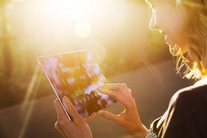 Woman using iPad at sunset
