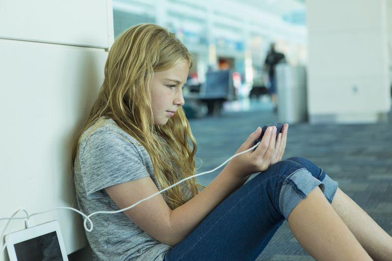 Young girl looking at her phone while its charging in an airport terminal.