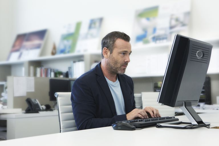 older man working on computer in small modern office