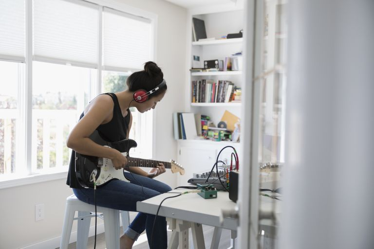 Teenage girl playing electric guitar, recording music in home office