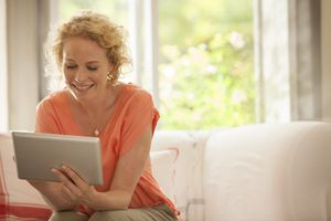Woman sitting on the couch reading on iPad tablet