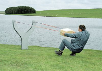 A man placing a large package in a big slingshot.