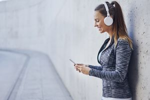 A young woman with headphones on, listening to music from her iPhone.
