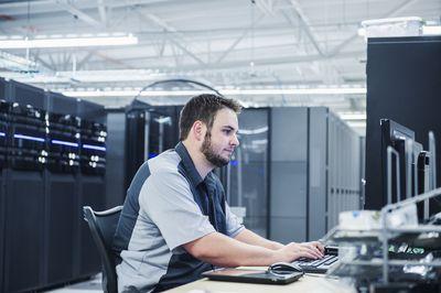Caucasian technician using computer in server room