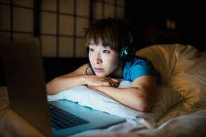 Someone streaming a movie while wearing headphones in the bed at night.