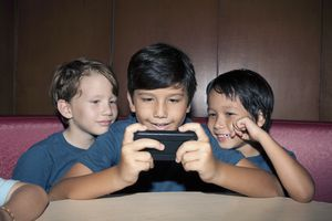 Three kids playing on an iPhone