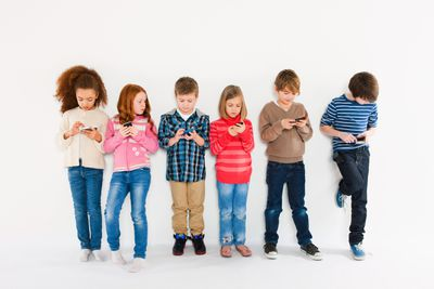 Children using smartphones, standing in a row against a white background.