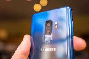 Someone holds up a blue Galaxy S9