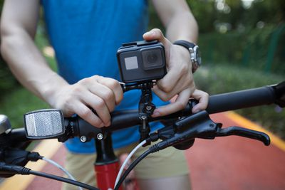 Cyclist mounting an action camera on mountain bike.