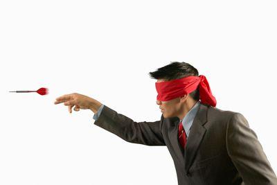 Blindfolded man throwing darts