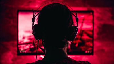 A veiw of a gamer from behind, with the background of a gaming screen tinted red.