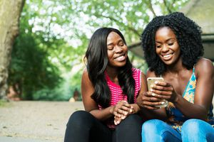 Two women laughing and looking at an iPhone
