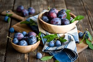 Plums in baskets on a cutting board on a table
