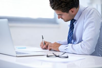 Man sitting at computer writing on a piece of paper
