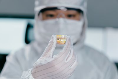 A scientist examining a computer chip in a laboratory setting.