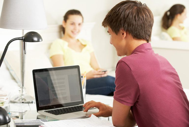 Teenage Boy Studying At Desk In Bedroom