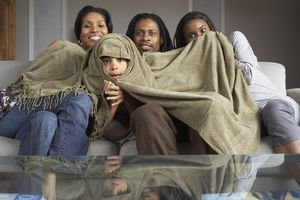 Family watching TV with young boy wrapped in a blanket
