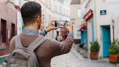 A man wearing a backpack and taking a photo with his smartphone while traveling internationally.