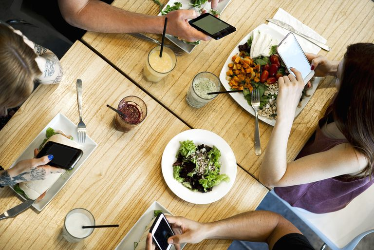 Diners using smartphones in restaurant