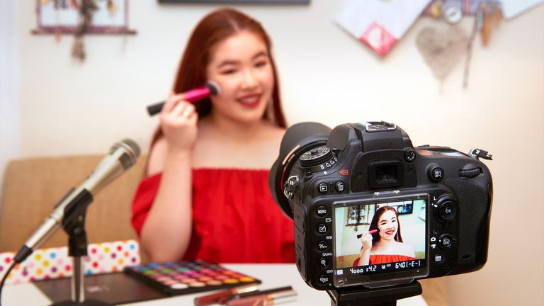A female social media influencer recording a makeup tutorial video.