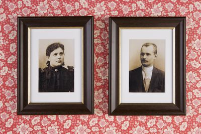 Two old-timey photos hanging on a wall.
