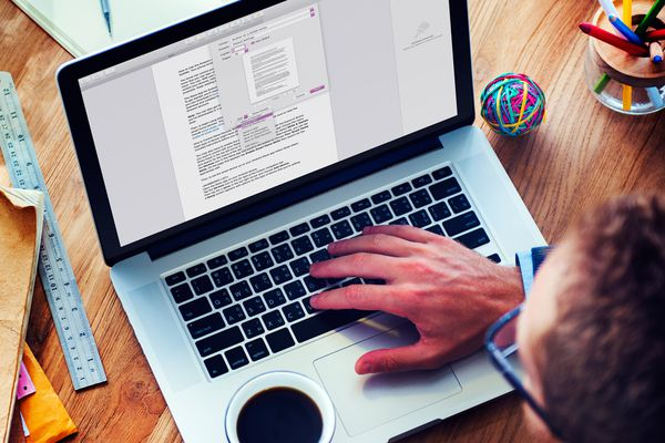 A man saving a Pages document as a PDF in Pages on a MacBook Pro.