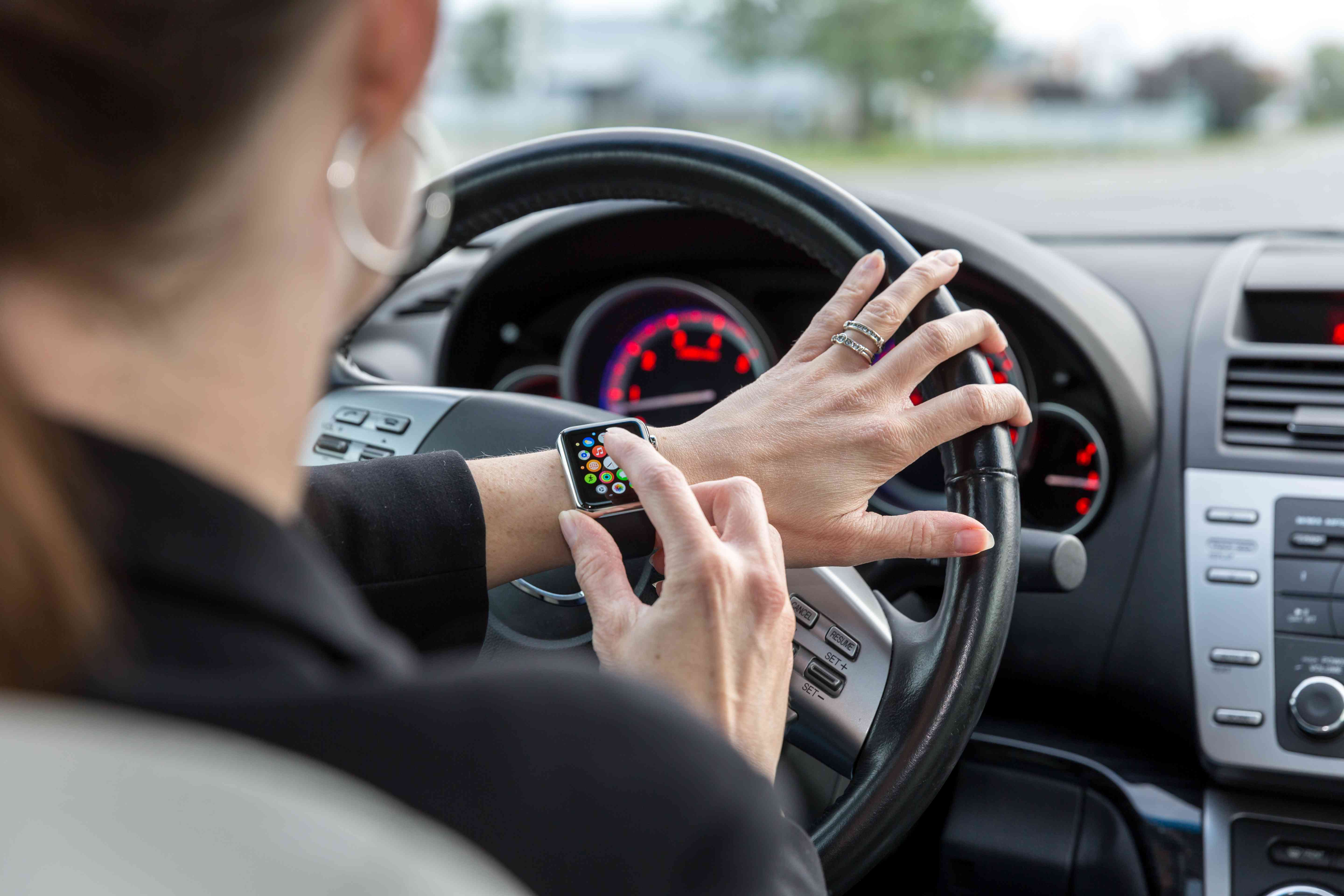Woman wearing Apple Watch while driving a car