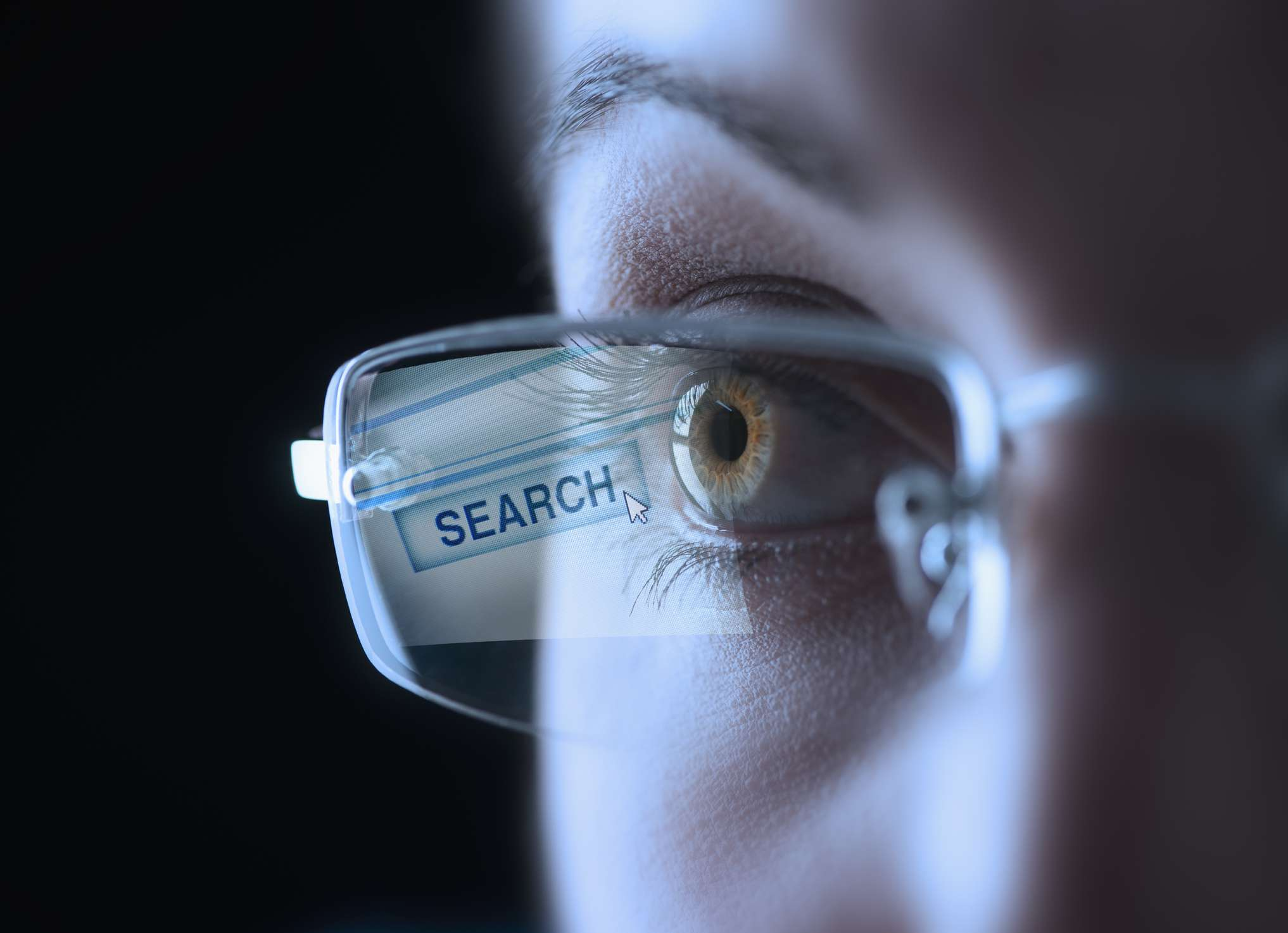 Coseup of a human eye, wearing glasses with a Search button reflecting on the lens.