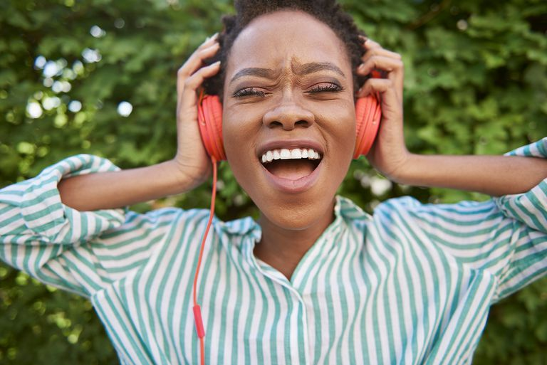 Portrait of singing young woman with headphones