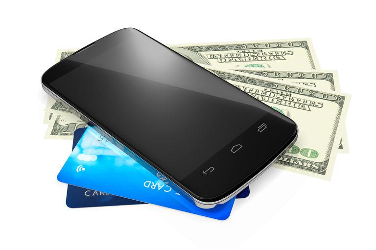 High Angle View Of Mobile Phone On Us Paper Currency And Credit Cards Over White Background