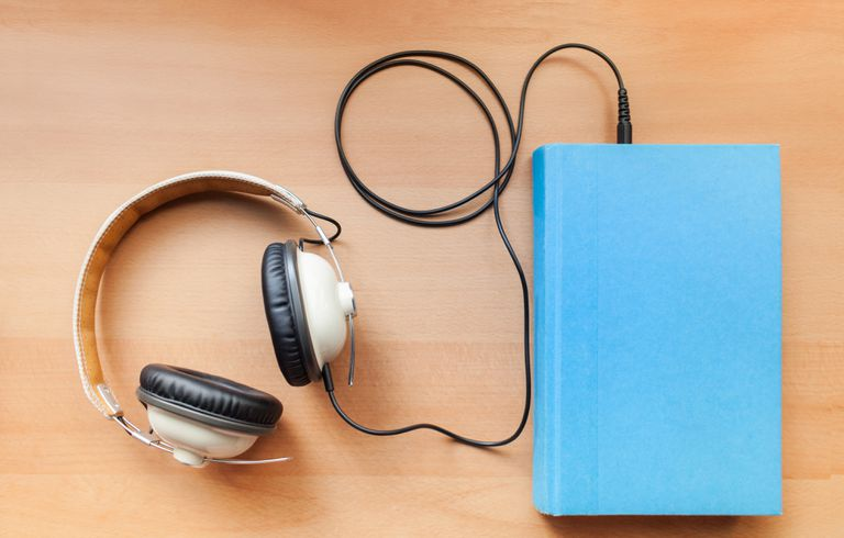 Pair of headphones plugged into a book