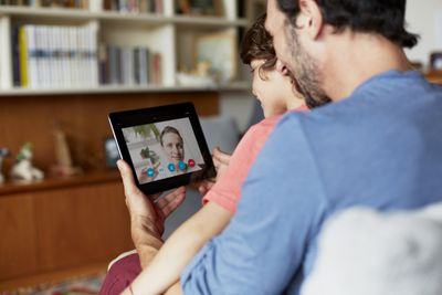 A parent and child use an iPad to Skype with another user