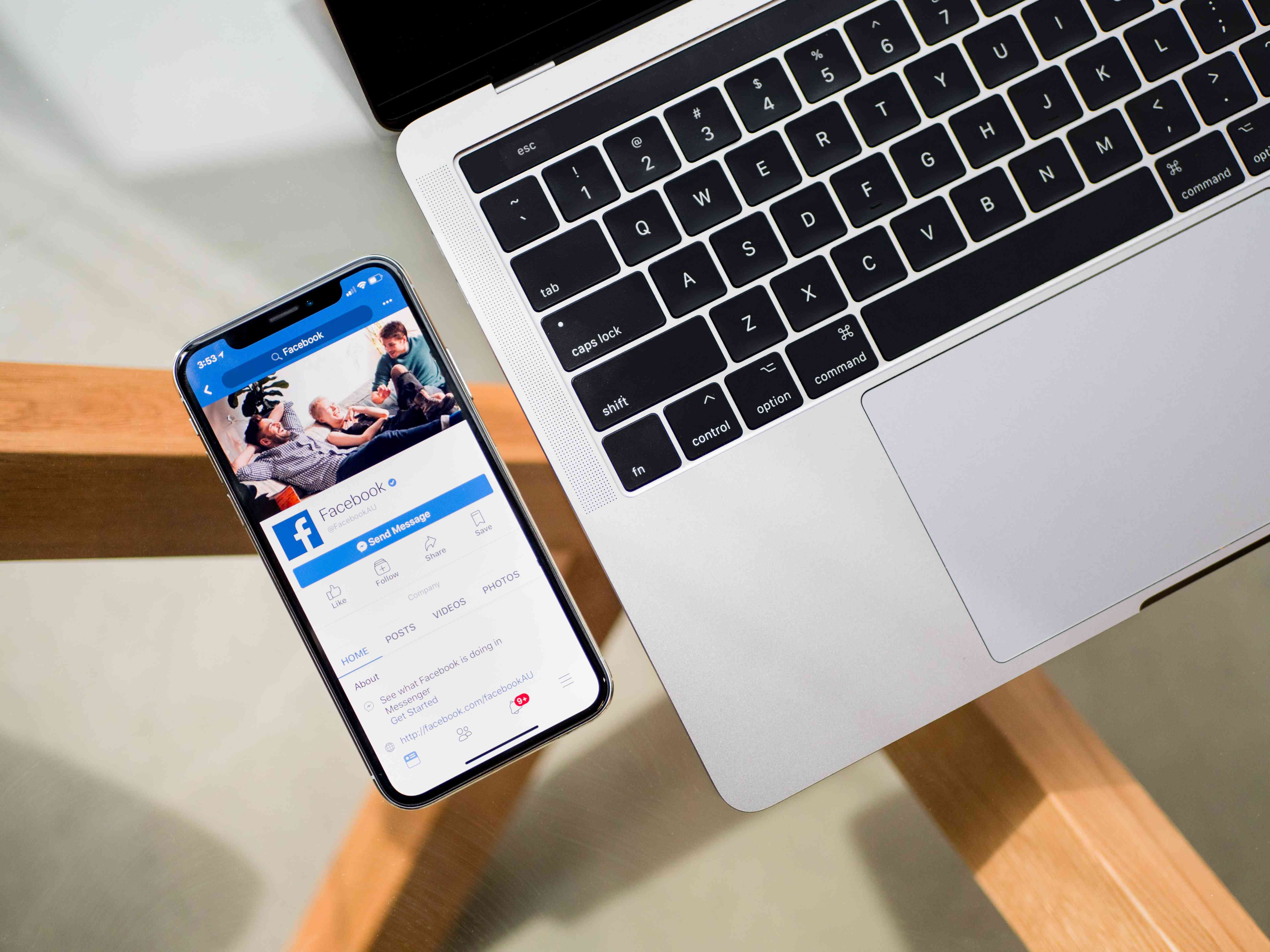 An iPhone X beside a laptop showing information about the Facebook app on the phone screen.