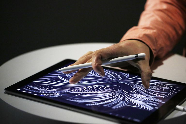 A man uses the new Apple Pencil on an iPad Pro
