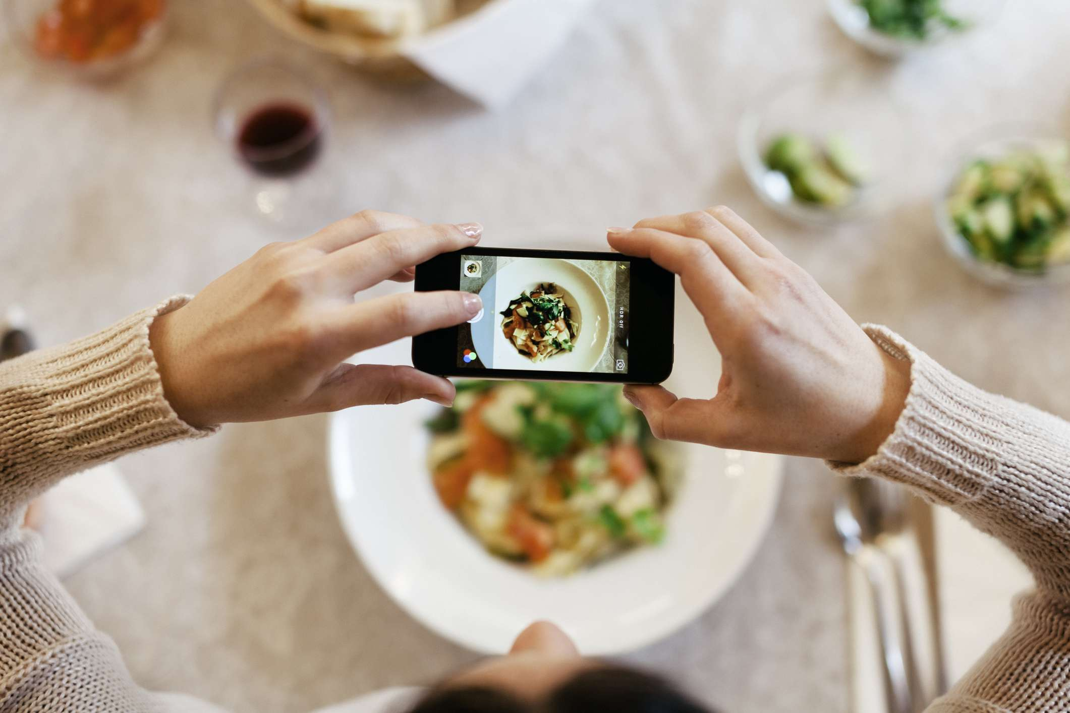 An image of someone taking a photo of their meal with their smartphone.