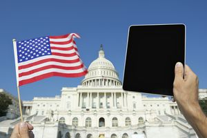 Hands holding American flag and digital tablet at the White House
