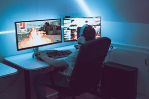 A person sitting at a desk with headphones in, looking at two screens depicting a game