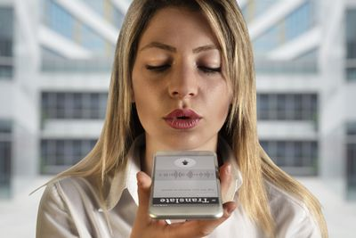 Woman speaking into a mobile device showcasing a translation app