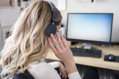 Caucasian woman listening to headphones at computer desk