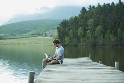 Figure 1-1: A screen shot showing a man using a laptop sitting on the edge of a pier overlooking a lake.