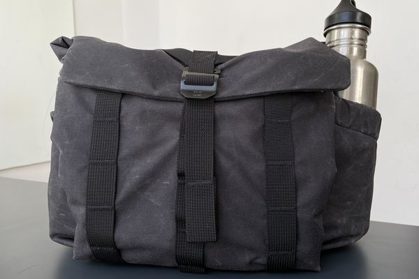 The Wotancraft Pilot camera bag, shown closed with a water bottle in a pocket on the side.
